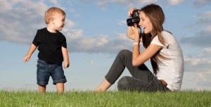 mae-tirando-foto-de-filho-no-gramado-com-camera-profissional